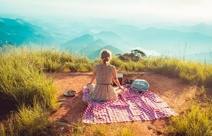 girl in dress on picnic mat outside in grass